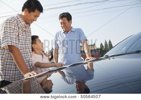 Family standing next to the car and looking at the map