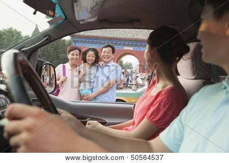 Parents driving and saying good bay to son and grandparents