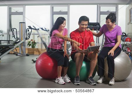 People looking at digital tablet in the gym