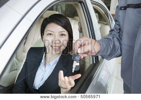 Mechanic Handing Keys to Businesswoman