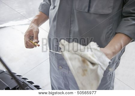 Mechanic Wiping Down Dipstick