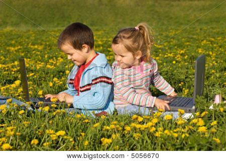 Kids With Laptops On The Flower Field
