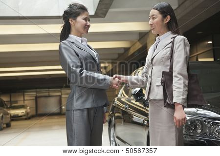 Two young businesswomen shaking hands in parking garage