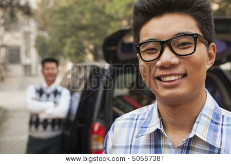 Portrait of boy in front of car on college campus