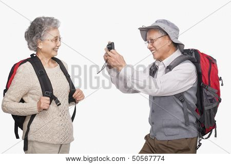 Senior man taking wife's picture with digital camera