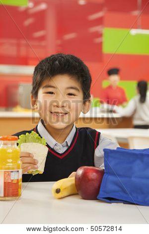 School boy portrait eating lunch in school cafeteria