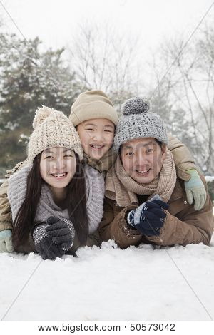 Family laying in snow for portrait