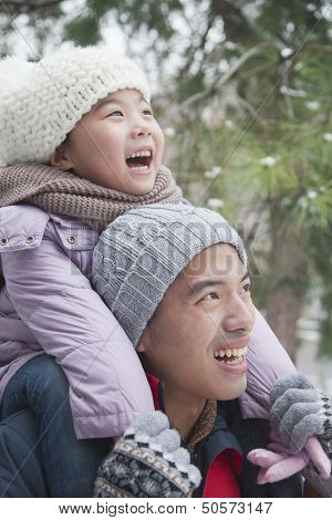 Father carrying daughter on shoulders in winter