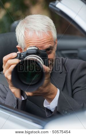 Mature paparazzi taking picture with professional camera hiding himself in his car