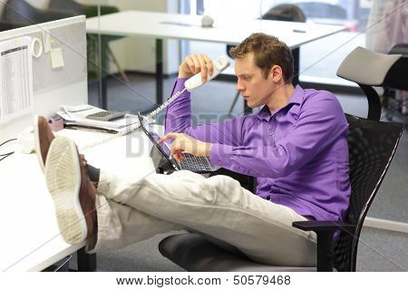 Young businessman caucasian in his office on phone working with tablet - bad sitting posture