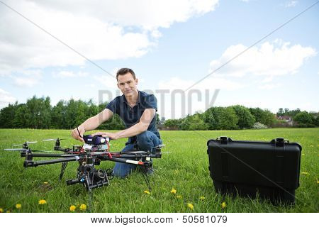 Portrait of young technician assembling octocopter drone crouching in park