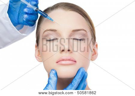 Content attractive model on white background having botox injection on the forehead
