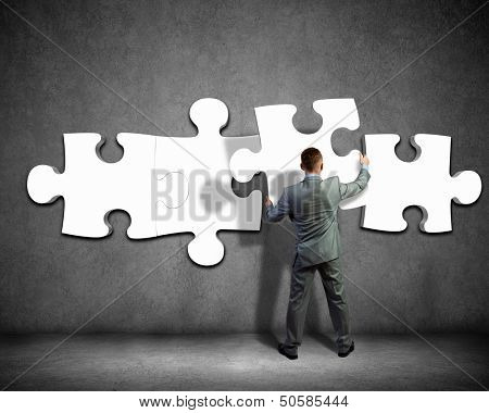 Image of businessman compiling macro white puzzle. Building business