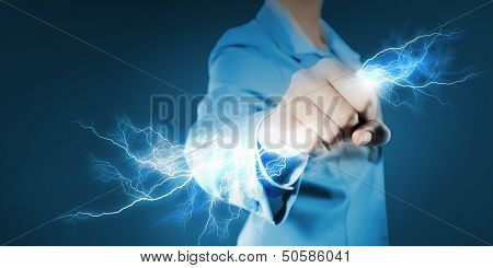 Image of powerful businesswoman holding lightning in fist