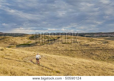 a lonely male biking over rolling prairie illuminated by sunrise at Soapstone Prairie Natural Area in northern Colorado near Fort Collins, late summer