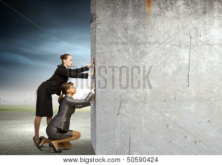 Two businesswoman pushing blank wall. Place for text