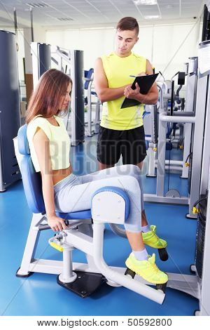 Girl and trainer engaged in simulator in gym