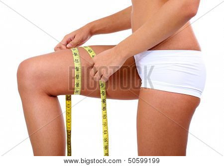 Beautiful young woman measuring her body with tape isolated on white