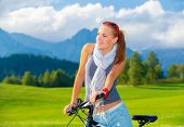 Portrait of cute cyclist girl resting in mountains, traveling on bicycle along Austrian mountains, e