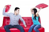 picture of pillow-fight  - Couple fight on red sofa isolated on white background - JPG