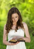 image of humble  - Beautiful woman with Bible is in sunny nature - JPG