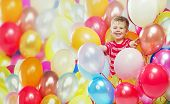 Small boy holding bunch of balloons