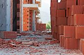 stock photo of untidiness  - Stack of red building blocks on an untidy construction site - JPG