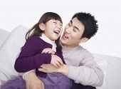 foto of tickle  - Father tickling daughter on the sofa - JPG