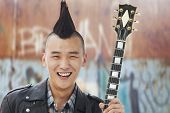 foto of half-shaved hairstyle  - Young man with punk Mohawk holding guitar - JPG