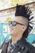 stock photo of half-shaved hairstyle  - Young man with punk Mohawk smiling - JPG
