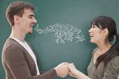 foto of ponytail  - Portrait of smiling male teacher and student in front of chalkboard holding hands - JPG