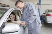 Mechanic Explaining to Businesswoman