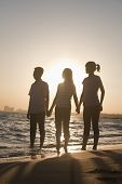 Family holding hands on the beach, sunset