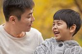 stock photo of mid autumn  - Father and son laughing in the park in autumn - JPG