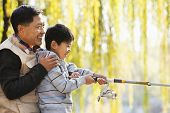 stock photo of weeping willow tree  - Father and son fishing together at lake - JPG