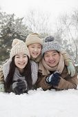image of cold-shoulder  - Family laying in snow for portrait - JPG