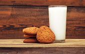 stock photo of oats  - glass of milk and oat cookies on wooden background - JPG