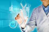 stock photo of biotechnology  - Woman scientist touching DNA molecule image at media screen - JPG