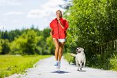 pic of dog park  - Young attractive sport girl running with dog in park - JPG