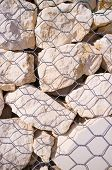 pic of rip-rap  - Detail take of stones behind the mesh of a gabion wall - JPG