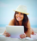 Young beautiful woman in swimming suit using her tablet on the beach