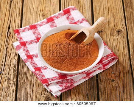 bowl of ground cinnamon with immersed wooden spoon