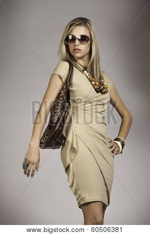 Blonde woman with sun glasses and animal print handbag