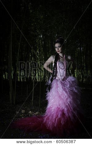 Portrait of fantasy woman in pink couture dress standing in a dark forest