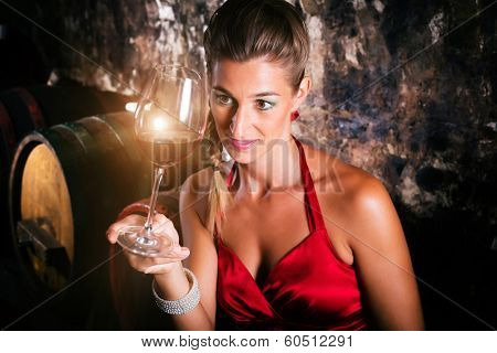 Woman in wine cellar with barrels tasting glass of vintage red