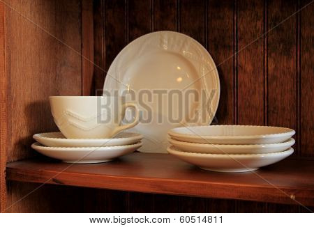 White glazed stoneware on warm-tone wood shelf