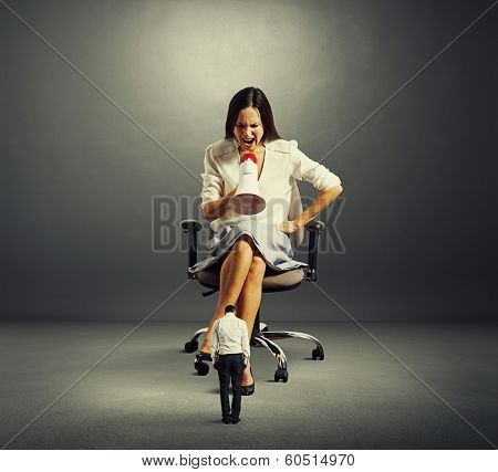 dissatisfied woman sitting on the office chair and screaming at small man