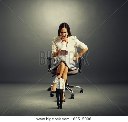 dissatisfied businesswoman screaming at small stressed man over dark background