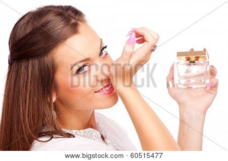 Beautiful brunette smelling perfume from her hand and looking at camera, isolated on white