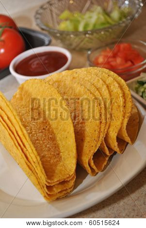 Close-Up of Taco Shells with Ingredients in the Background